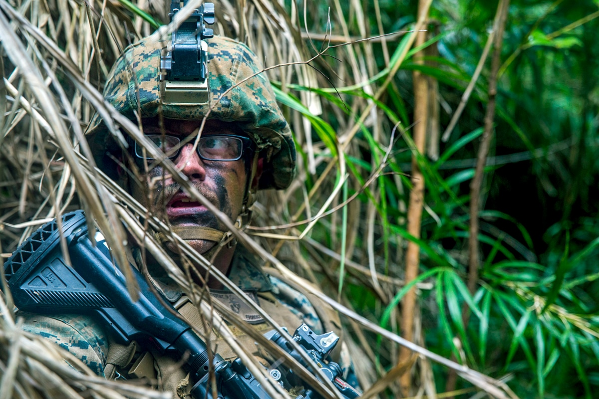 A Marine wearing camouflage paint holding a weapon gives a sideways glance while positioned behind straw.