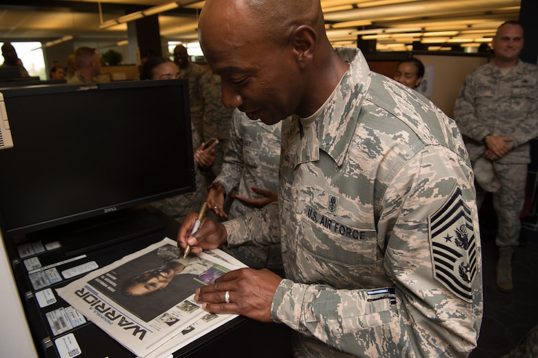 Chief Master Sgt. of the Air Force Kaleth O. Wright signs a copy of the Peninsula Warrior at Joint Base Langley-Eustis, Va. June 28, 2018. Wright toured JBLE for two days seeing the day-to-day operations of the different wings and units here. (U.S. Air Force photo by Senior Airman Tristan Biese)