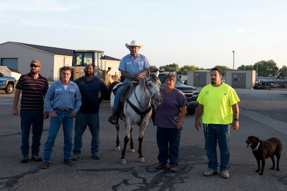 17th Civil Engineer Squadron heavy equipment operator, George Nava poses with other heavy equipment operators, called the dirt boys, at Goodfellow Air Force Base, Texas, June 29, 2018. Nava began his last day, before retirement, by checking off an item on his bucket list, riding to work on his horse. (U.S. Air Force photo by Airman 1st Class Zachary Chapman/Released)