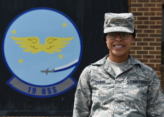 A female in uniform stands outside in front of a blue emblem with the words 19 OSS.