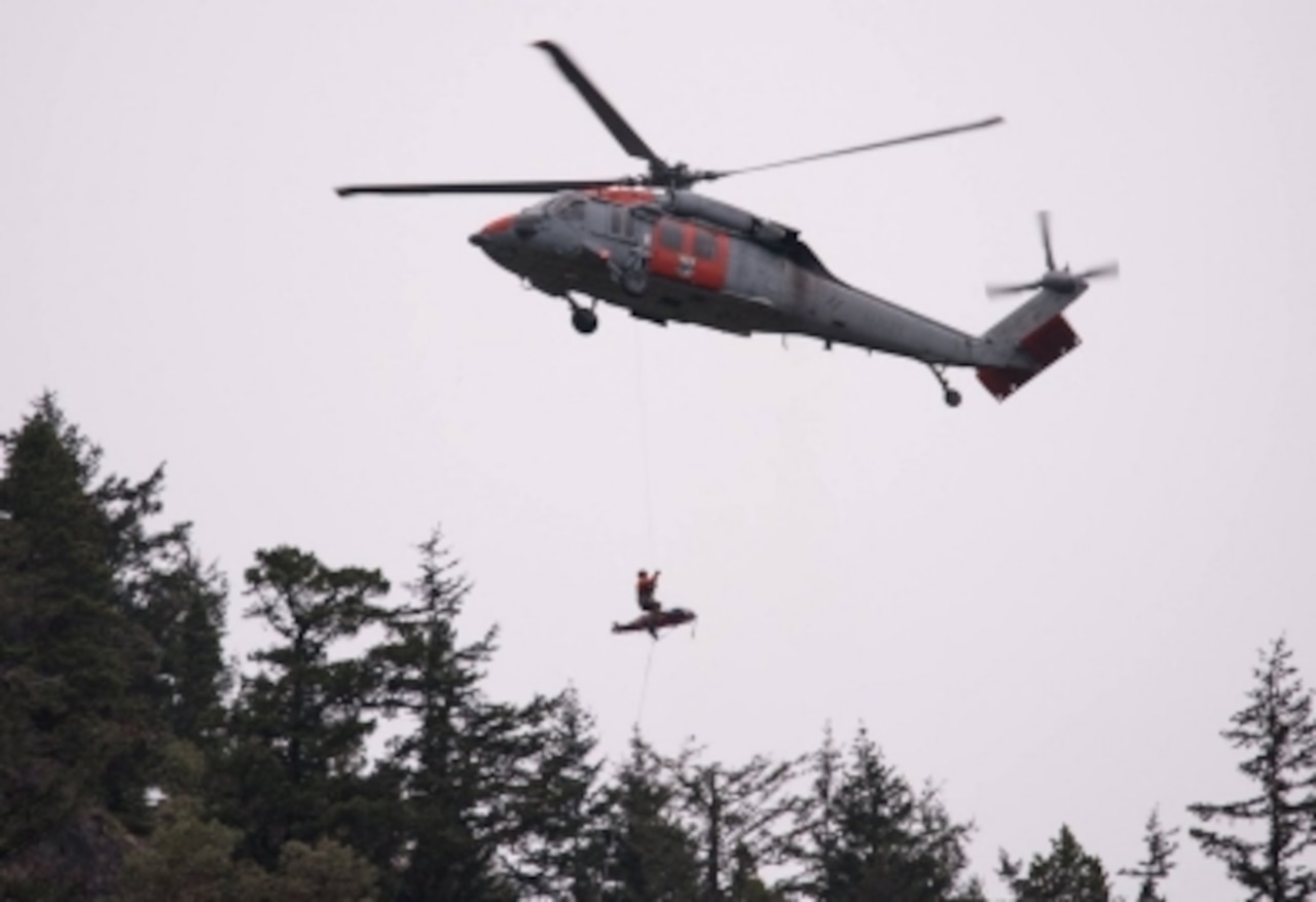 A hiker is hoisted aboard a helicopter.