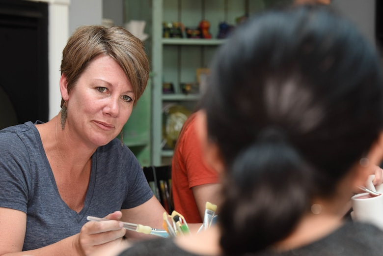 Paula Walker, the spouse of Chief Master Sgt. Justin Walker, 28th Mission Support Group superintendent, paints a piece of pottery and talks to another spouse during an event held by the 28th Bomb Wing Chapel in Rapid City, S.D., June 26, 2018. Multiple spouses came out to a pottery and painting activity hosted by the 28th Bomb Wing Chapel and went out to dinner afterward. (U.S. Air Force photo by Airman 1st Class Thomas Karol)