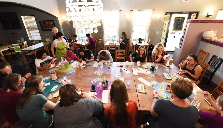 Spouses of deployed and remote Airmen and base members gather and paint various pieces of pottery in Rapid City, S.D., June 26, 2018. The 28th Bomb Wing Chapel hosted an event where spouses came out to paint pottery and form a network with other spouses. (U.S. Air Force photo by Airman 1st Class Thomas Karol)