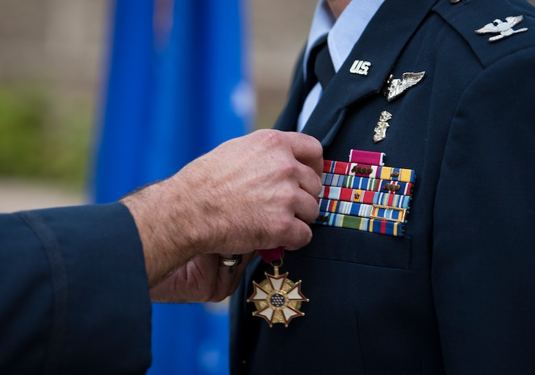 Col. Cavan Craddock, 99th Air Base Wing commander, awards a Legion of Merit to Col. Virginia Garner, 99th Medical Group commander during a change of command ceremony at Nellis Air Force Base, Nevada, June 29, 2018. The Legion of Merit is awarded for exceptional service. (U.S. Air Force photo by Airman 1st Class Andrew D. Sarver)