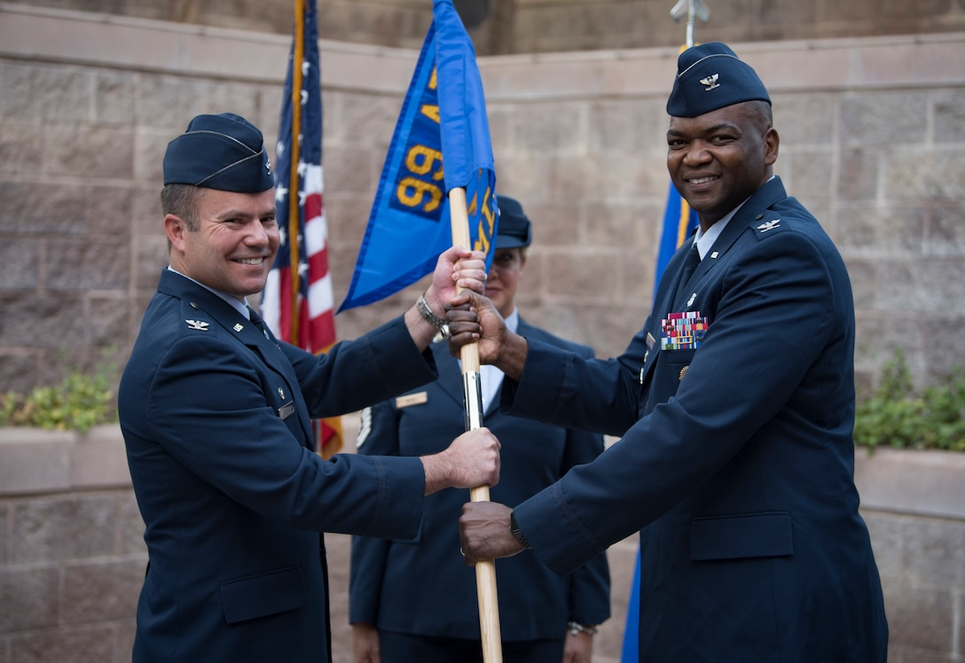 Col. Alfred Flowers Jr., 99th Medical Group incoming commander, assumes command from Col. Cavan Craddock, 99th Air Base Wing commander, during a change of command ceremony at Nellis Air Force Base, Nevada, June 29, 2018. Flowers' last command was for the 52nd Medical Group at Spangdahlem Air Base, Germany. (U.S. Air Force photo by Airman 1st Class Andrew D. Sarver)