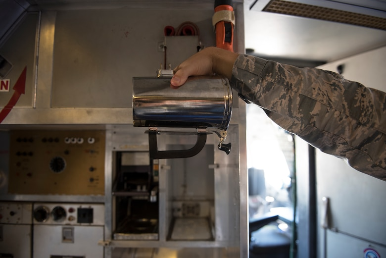 An Airman holds a hot cup inside a KC-10 Extender at Travis Air Force Base, Calif., June 21, 2018. The base is working on developing a new handle for the cup which could save the Air Force thousands. (U.S. Air Force photo by Tech. Sgt. James Hodgman)