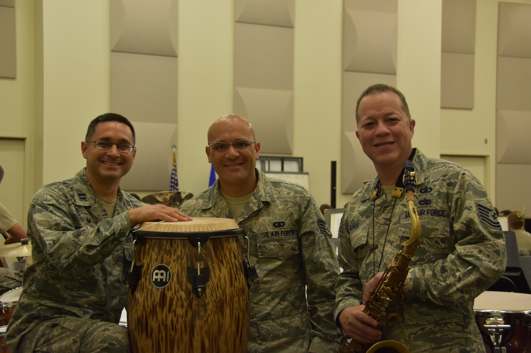 From left, U.S. Air Force Capt. Rafael Toro-Quiñones, commander and conductor of the Band of the Golden West, U.S. Air Force Staff Sgt. Wilfredo Cruz, on solo percussion and Tech. Sgt. Marco Muñoz, composer, pose for a photo during rehearsal at Travis Air Force Base, California, June 22, 2018. (U.S. Air Force photo by Senior Airman Mary Gant/Released)