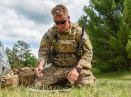 Senior Airman Ethan Johnson, an Explosive Ordnance Disposal technician with the 119th Wing in Hector Field, North Dakota, plans his teams route June 25, 2018, for the Audacious Warrior land navigation compass course at Fort McCoy, Wisconsin. The course allowed Airmen to practice  their skills in map reading, compass use, and pace counting.