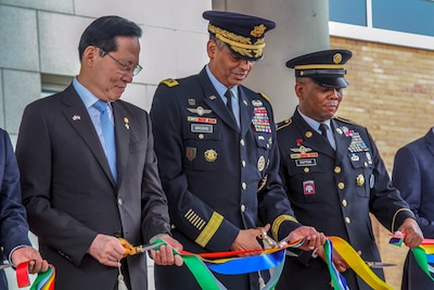 Three people stand shoulder to shoulder and cut a ribbon.