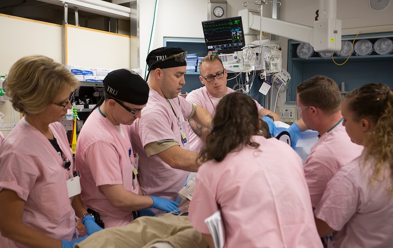 Maj. Shane Runyon, Baltimore's Center for the Sustainment of Trauma and Readiness Skills (C-STARS) program deputy director, and Master Sgt. Sean Patterson, a respiratory therapist and superintendent of C-STARS Baltimore, work with staff and students on a newly arrived patient at the Trauma Resuscitation Unit (TRU) at the University of Maryland Medical Center, Baltimore, June 13, 2018. The U.S. Air Force's C-STARS Baltimore program partners with the R Cowley Shock Trauma Center at the University of Maryland Medical Center to ensure medical Airmen train on the latest trauma care techniques by embedding them in the clinic and giving them first-hand experience treating trauma patients. (Courtesy photo)