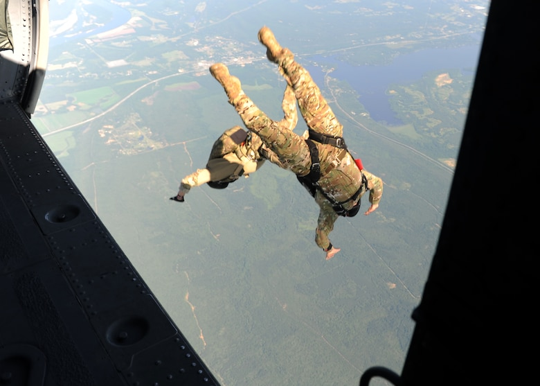 People in uniform perform and prepare for freefall jumps.