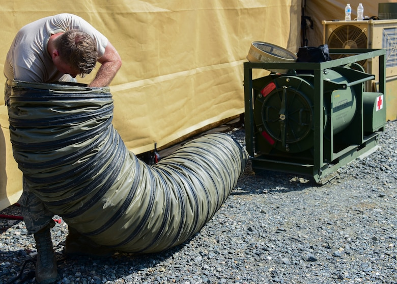 An Expeditionary Medical Systems exercise Airman assembles tent components at Joint Base Langley-Eustis, Va., June 20, 2018. A core group of Airmen were trained on tent assembly prior to the exercise and were then tasked with teaching exercise volunteers on the newly learned procedures. (U.S. Air Force photo by Airman 1st Class Monica Roybal)