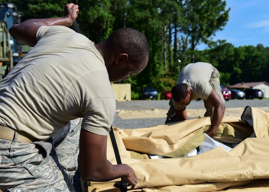 Staff Sgt. Matthew Bryles, 633rd Civil Engineer Squadron emergency management technician, and Senior Airman Bryce Carter, 633rd CES heating, ventilation and air conditioning technician, assemble tent components at Joint Base Langley-Eustis, Va., June 20, 2018. Exercise volunteers learned which new components worked interchangeably with both tents on display. (U.S. Air Force photo by Airman 1st Class Monica Roybal)