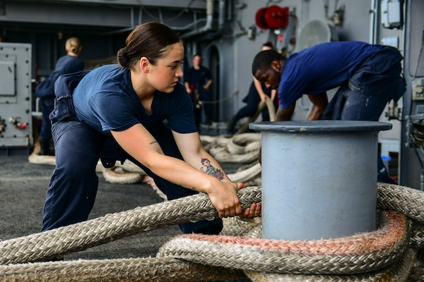 Seaman handles mooring line on fantail of aircraft carrier USS Theodore Roosevelt during regularly scheduled port visit to Singapore, April 2, 2018 (U.S. Navy/Michael Colemanberry)