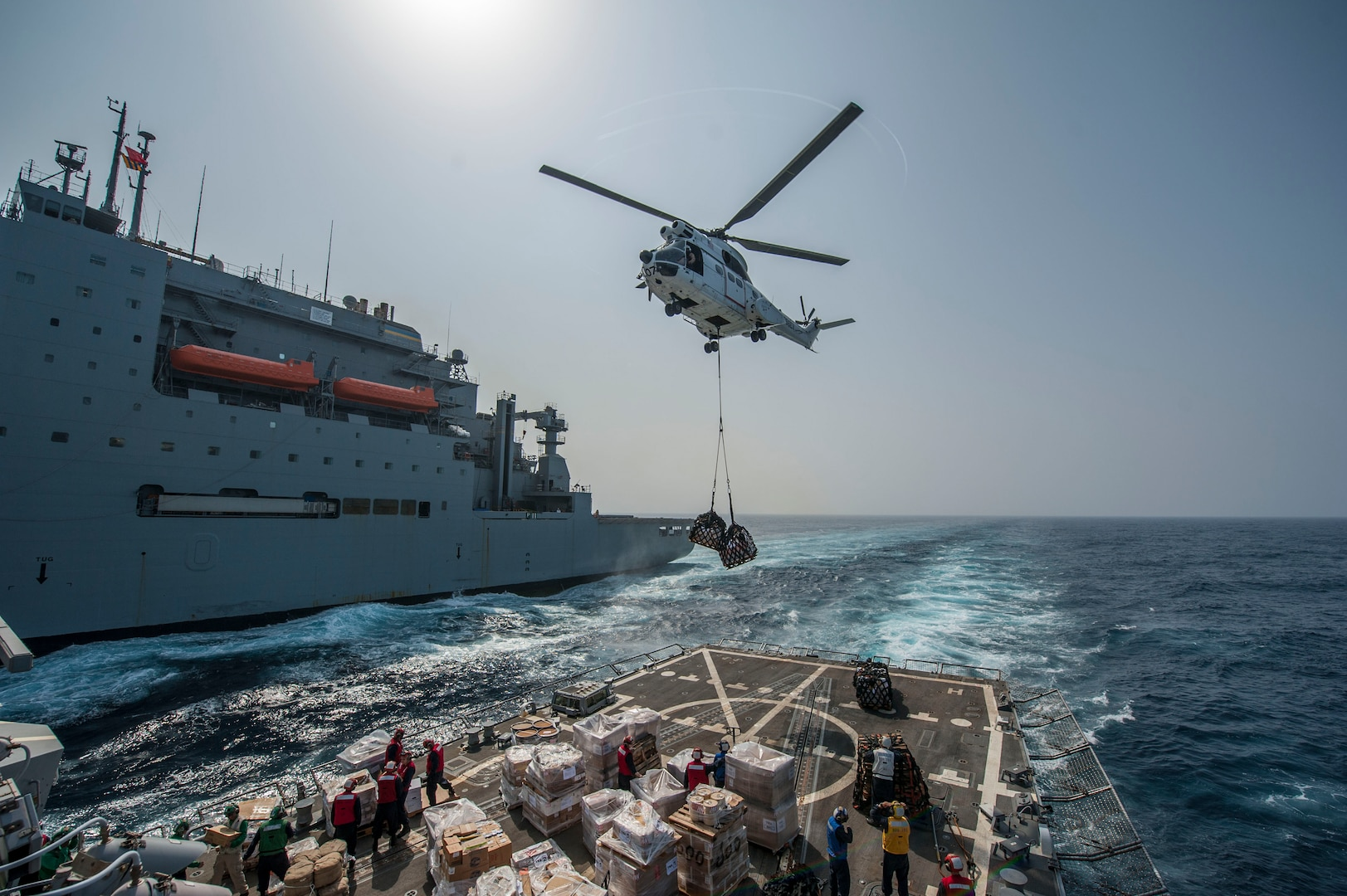 SA-330J Puma helicopter drops supplies on flight deck of USS Truxtun during vertical replenishment with Military Sealift Command dry cargo and ammunition ship USNS Richard E. Byrd, Red Sea, April 12, 2014 (U.S. Navy/Scott Barnes)
