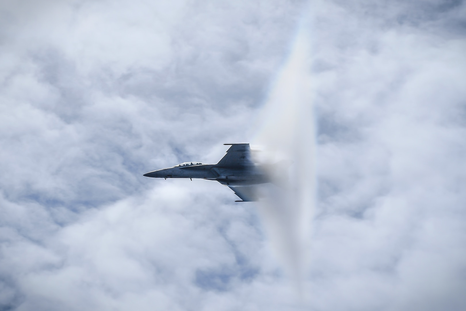 F/A-18F Super Hornet, assigned to Fighting Redcocks of Strike Fighter Attack Squadron (VFA) 22, breaks sound barrier over aircraft carrier USS Theodore Roosevelt during airpower demonstration, Pacific Ocean, May 3, 2018 (U.S. Navy/Spencer Roberts)