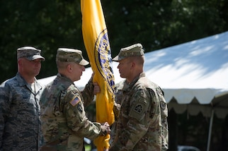 Lt. Gen. Jeffrey Buchanan (right) passes the Joint Task Force Civil Support (JTF-CS) flag to Maj. Gen. William Hall (left) during a change of command ceremony held at Seay Plaza on Fort Eustis. The passing of the flag symbolizes the passing of authority from one commander to another. Hall assumed authority of JTF-CS from Maj. Gen. Richard Gallant June 29, and is now JTF-CS's tenth commanding general. (Official DoD photo by Christopher Thompson/released)