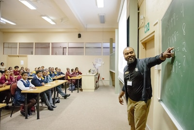Professor teaches South African students in classroom.