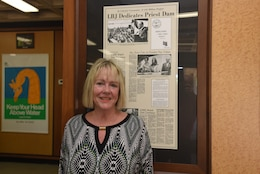 Harriett Priest, daughter of the late Congressman J. Percy Priest, poses by a historical news clipping at the J. Percy Priest Lake Visitor's Center.  She visited following the 50th Anniversary of J. Percy Priest Dam and Reservoir at the dam in Nashville, Tenn., June 29, 2018. (USACE Photo by Lee Roberts)