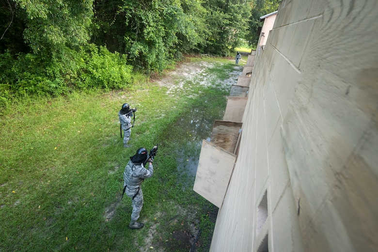 Airmen from the 23d Security Forces Squadron (SFS) take aim at an opposing assailant during a Force on Force training scenario, June 29, 2018, at Moody Air Force Base, Ga. This training was held to ensure SFS Airmen are proficient in various tactics and procedures such as: building clear out, team movements, hostage rescue and properly applying cover fire. The scenario required Airmen to maneuver through multiple buildings to rescue a simulated victim guarded by opposing forces. (U.S. Air Force photo Airman 1st Class Eugene Oliver)