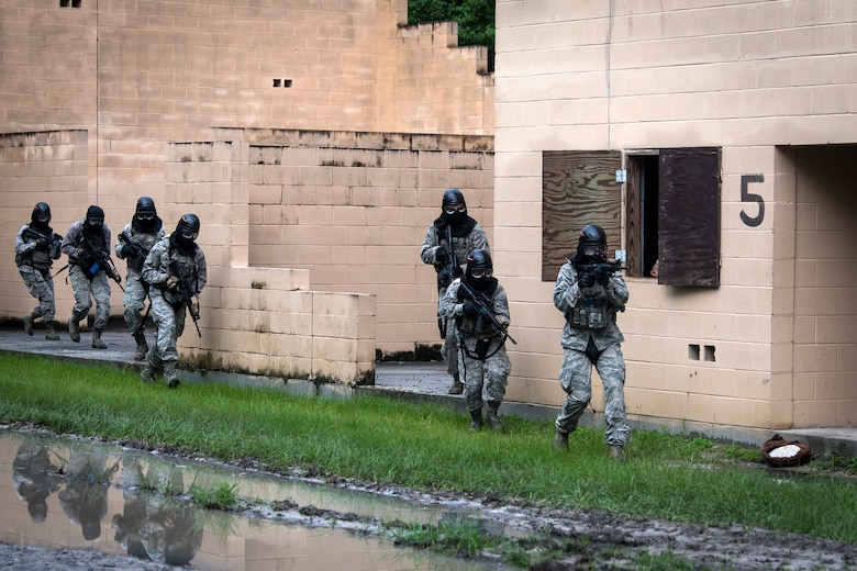 Airmen from the 23d Security Forces Squadron (SFS) run to the next building while providing cover fire during a Force on Force training scenario, June 29, 2018, at Moody Air Force Base, Ga. This training was held to ensure SFS Airmen are proficient in various tactics and procedures such as: building clear out, team movements, hostage rescue and properly applying cover fire. The scenario required Airmen to maneuver through multiple buildings to rescue a simulated victim guarded by opposing forces. (U.S. Air Force photo Airman 1st Class Eugene Oliver)