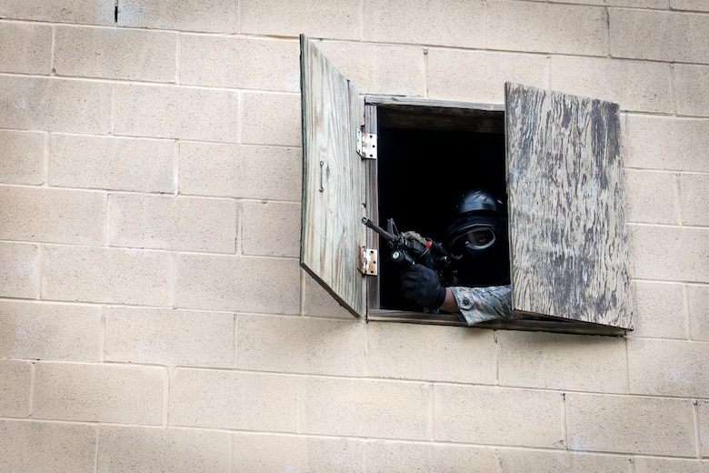 An Airman from the 23d Security Forces Squadron (SFS) defends his position during a Force on Force training scenario, June 29, 2018, at Moody Air Force Base, Ga. This training was held to ensure SFS Airmen are proficient in various tactics and procedures such as: building clear out, team movements, hostage rescue and properly applying cover fire. The scenario required Airmen to maneuver through multiple buildings to rescue a simulated victim guarded by opposing forces. (U.S. Air Force photo Airman 1st Class Eugene Oliver)
