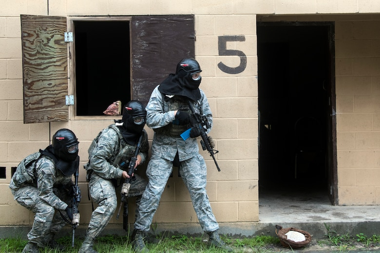 Airmen from the 23d Security Forces Squadron (SFS) prepare to clear a building during a Force on Force training scenario, June 29, 2018, at Moody Air Force Base, Ga. This training was held to ensure SFS Airmen are proficient in various tactics and procedures such as: building clear out, team movements, hostage rescue and properly applying cover fire. The scenario required Airmen to maneuver through multiple buildings to rescue a simulated victim guarded by opposing forces. (U.S. Air Force photo Airman 1st Class Eugene Oliver)