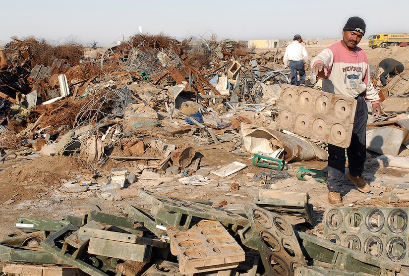 An Iraqi national separates scrap metal to be salvaged and recycled into cash while at Forward Operating Base Warhorse, located in Diyala, Iraq.