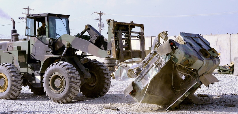A forklift driven by Army Pfc. Cody Taylor, wheeled vehicle mechanic, Materiel Readiness Branch, 1st Cavalry Division Resolute Support Sustainment Brigade, flips a vehicle as part of the Afghan National Defense Security Forces 1050 DEMIL Program at Bagram Airfield, Afghanistan.