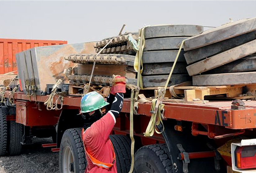 A foreign national augmentee at a mobile redistribution yard tightens the straps on a load of scrap metal at Joint Base Balad, Iraq. The scrap metal is to be delivered to DLA Disposition Services so that it can be disposed of properly.