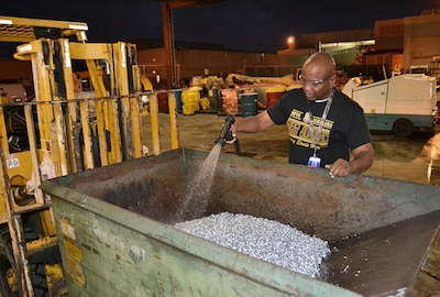 Charles Miller, a Fleet Readiness Center Southeast material identifier, washes a bin of aluminum scraps. Washing the scraps removes oil residue and dust so the metal can be taken to DLA Disposition Services for resale.