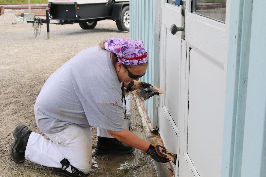 Paint Shop team member Jill Clark uses epoxy to patch a door at Arnold Air Force Base. (U.S. Air Force photo/Bradley Hicks) (This image was manipulated by obscuring badges for security purposes)