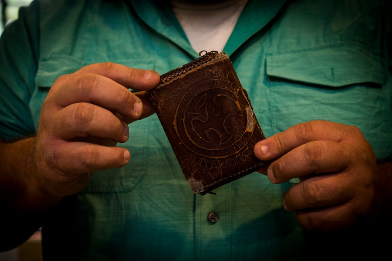 Former Army Sgt. Tony Fantasia displays the wallet that he attributes saving his life at his shop in San Antonio, Texas, June 29th, 2018. Working with leather has aided Fantasia's battle with PTSD that he developed after his deployments to Southwest Asia as a medic. He now runs an outreach program for veterans focusing on various artistic outlets. (U.S. Air Force photo by Senior Airman Keifer Bowes)