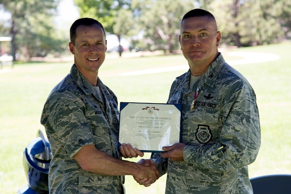 PETERSON AIR FORCE BASE, Colo. – Col. Todd Moore, 21st Space Wing commander, presents the Legion of Merit to Col. Eric Dorminey, 21st Space Wing outgoing vice commander, at a going away barbecue at Capt. Lyon Memorial Park at Peterson Air Force Base, Colorado, July 2, 2018. Dorminey became 21 SW vice commander in April, 2015, and spent nearly 39 months in the position. (U.S. Air Force photo by Robb Lingley)