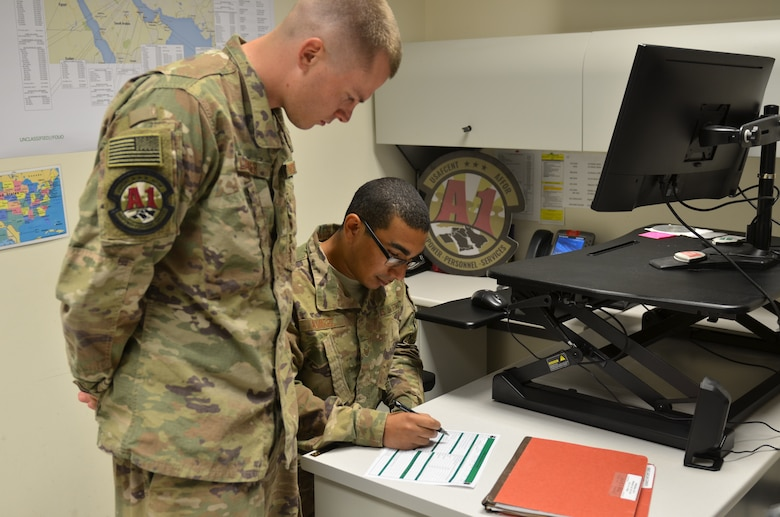 Senior Airman Joshua Glazier, U.S. Air Force Central Command deliberate and crisis action planning and execution segment operator, and Staff Sgt. Eric Alvarez, AFCENT personnel operator, review pre-deployment checklists at Al Udeid Air Base, Qatar, June 12, 2018. Manpower, Personnel and Services Directorate (A1) recently reduced the length of pre-deployment checklists in order to reduce redundancy and give more time for Airmen to spend with their families. (U.S. Air Force photo by Staff Sgt. Caitlin Conner)