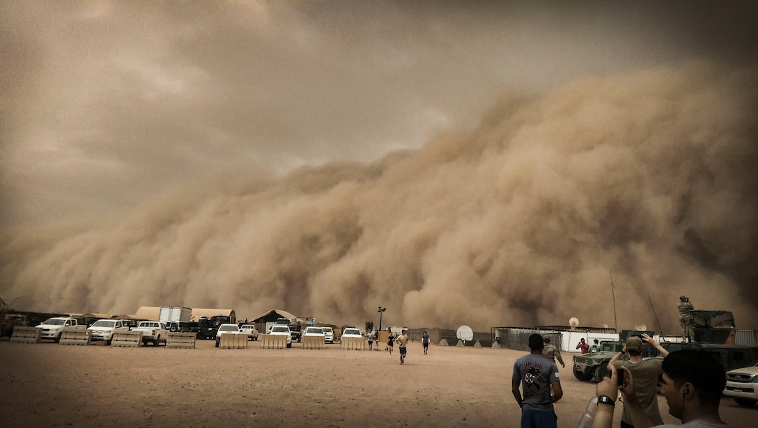 U.S. service members observe and take photos of a sand storm at Nigerien Air Base 201, Niger, June 24, 2018. This was the largest sand storm of the season so far, with sustained winds in excess of 50 knots. (U.S. Air Force courtesy photo by Master Sgt. William S. McDuffie)