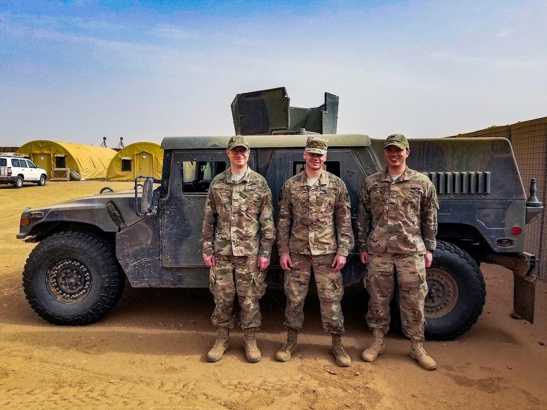 U.S. Air Force Master Sgt. Corey Reimer, left, 724th Expeditionary Air Base Squadron weather flight chief, stands alongside U.S. Air Force weather forecasters, Senior Airman Samuel Batterson, middle, and Airman 1st Class Anthony Montero at Nigerien Air Base 201, Niger, June 29, 2018. Air Base 201 was hit by four sandstorms throughout the last two weeks. The three-man weather team worked around the clock to forecast and keep base personnel and resources out of harm's way during the storms. (U.S. Air Force courtesy photo)