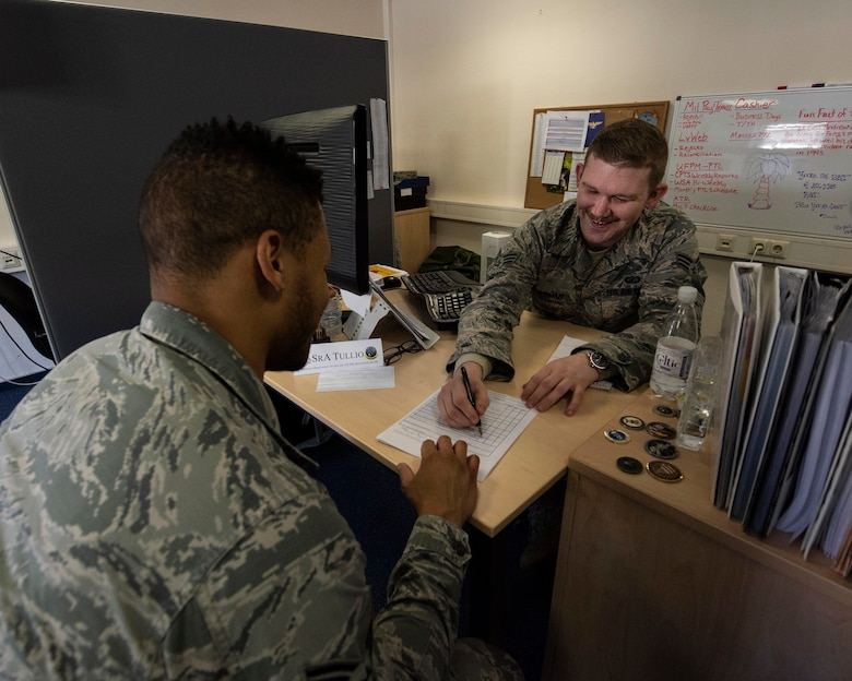Senior Airman Cody Chrisman, a military pay technician with the 194th Wing, assists Senior Airman Craig Harris, 52nd Comptroller Flight financial management technician, with financial checklist during training April 17, 2018 at Spangdahlem Air Base, Germany. Guardsmen from the 141st ARW and 194th Wing travelled to Spangdahlem to achieve training requirements, gain helpful tricks of the trade, as well as assist in task completion where possible.