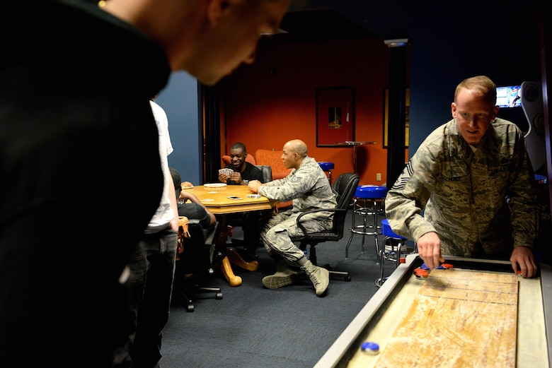 Chief Master Sgt. Johnathan Hover, 14th Flying Training Wing command chief, spreads sand across the shuffleboard table March 2, 2018. Dorm dinners allow senior leaders to show the junior enlisted members they can provide a positive service to others no matter the rank on their uniforms. (U.S. Air Force photo by Airman 1st Class Keith Holcomb)