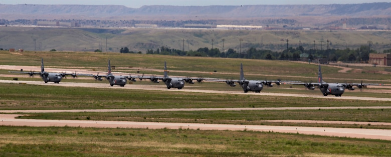 Five C-130 Hercules aircraft taxi on the Peterson Air Force Base, Colorado flightline, after formation flying during a training sortie hosted by the 302nd Airlift Wing, June 23, 2018.
