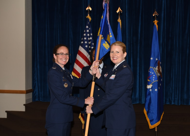 Colonel Stacy Jo Huser, 90th Missile Wing commander, passes the guidon to Col. Kristine Hackett, 90th Medical Group commander, during the 90th MDG change of command ceremony June 29, 2018, at F.E. Warren Air Force Base, Wyo. The ceremony signified the transition of command from Col. Cherron Galluzzo. (U.S. Air Force photo by Airman 1st Class Braydon Williams)