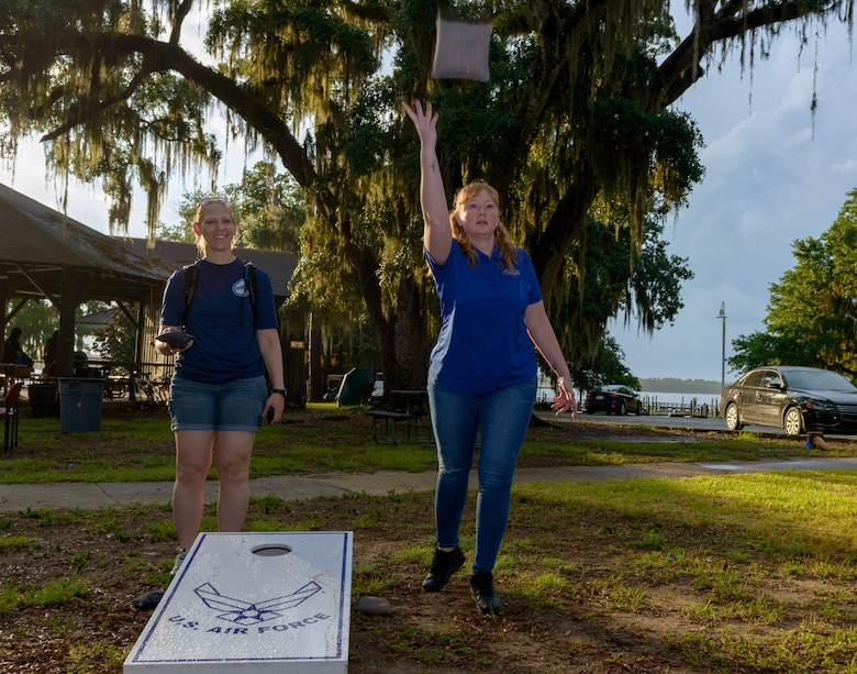 U.S. Air Force Maj. Erin Holland, 81st Force Support Squadron operations officer, and Master Sgt. Krista Mercadel, 81st FSS force management superintendent, play corn hole during Freedom Fest at Marina Park on Keesler Air Force Base, Mississippi, June 30, 2018. The event included carnival rides, a burger cook-off, hot wings and watermelon eating competitions and a fireworks display. (U.S. Air Force photo by Andre' Askew)