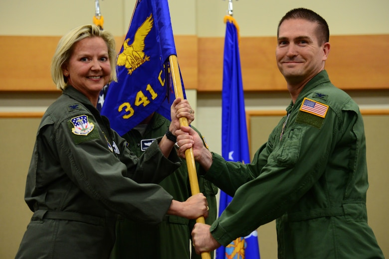 Col. Christopher Menuey, right, accepts command of the 341st Operations Group from Col. Jennifer Reeves, 341st Missile Wing commander, during an assumption of command ceremony July 3, 2018, at Malmstrom AFB, Mont.