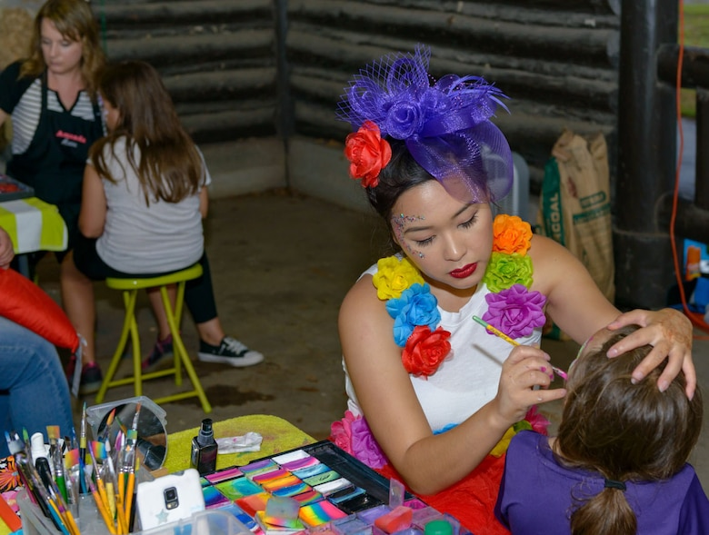 Catherine Ha, Copycats Face Painting owner, applies face paint to Keesler families during Freedom Fest at Marina Park on Keesler Air Force Base, Mississippi, June 30, 2018. The event included carnival rides, a burger cook-off, hot wings and watermelon eating competitions and a fireworks display. (U.S. Air Force photo by Andre' Askew)