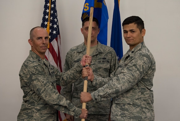 Col. Steven Behmer, U. S. Air Force Weapons School commandant, passes a guidon to Lt. Col. Douglas Medley, 32nd Weapons Squadron commander during an assumption of command ceremony at Nellis Air Force Base, Nevada, June 28, 2018. The 32nd WPS will focus on the Cyber Warfare Operations Weapons Instructor Course taught at the Weapons School. (U.S. Air Force photo by Airman 1st Class Andrew D. Sarver)