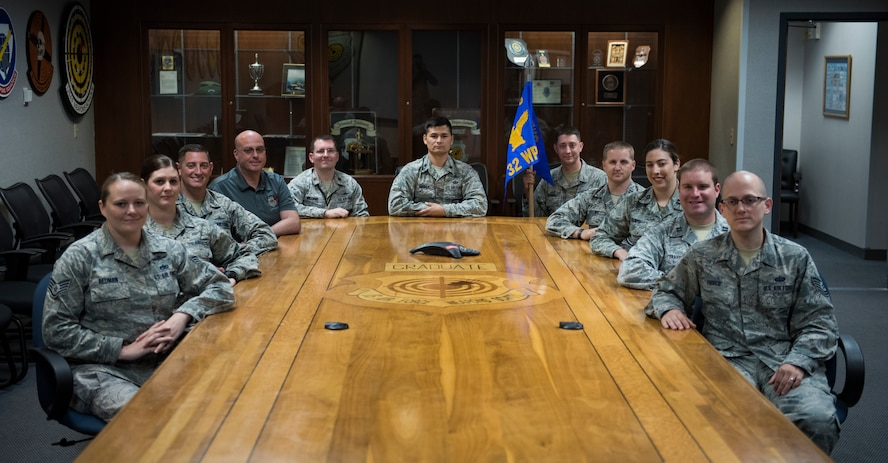 Members assigned to the 32nd Weapons Squadron gather around a table after an assumption of command ceremony at Nellis Air Force Base, Nevada, June 28, 2018. The 32nd WPS is the newest squadron in the U.S. Air Force Weapons School. (U.S. Air Force photo by Airman 1st Class Andrew D. Sarver)