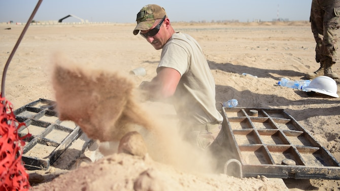 Senior Airman Austin Stimmel, 379th Expeditionary Civil Engineer Squadron cable and antenna systems technician, shovels dirt from a cable storage area at Cargo City, located at Abdullah Al Mubarak Air Base, Kuwait, June 25, 2018. Stimmel and his fellow Airmen are installing communications lines for the new operating location, slated to open later this year. (U.S. Air Force photo by Staff Sgt. Christopher Stoltz)