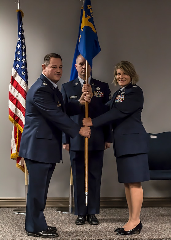 Col. Adam Willis, 445th Airlift Wing commander, passes the guidon to Col. Roberta Stemen, incoming 445th Aeromedical Staging Squadron commander, during an assumption of command ceremony June 2, 2018.