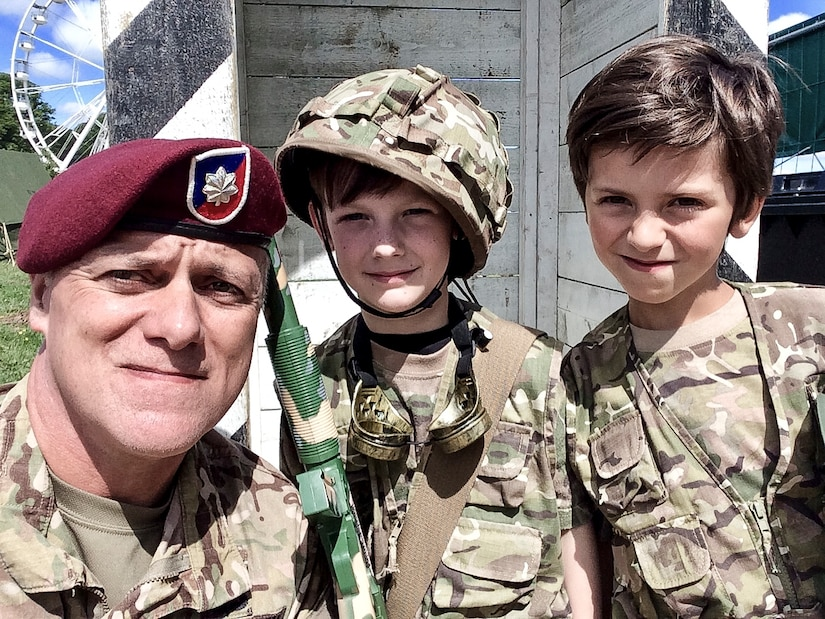 A soldier takes a photo with two French boys dressed as soldiers.