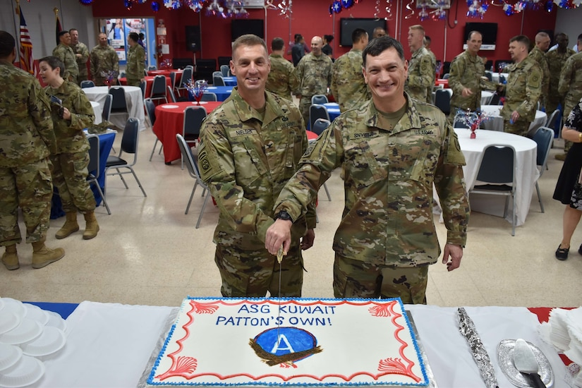 Col. Shannon Nielsen and Command Sgt. Maj. William Synder cut the ceremonial cake after the Area Support Group-Kuwait Change of Command on July 2, 2018 at Camp Arifjan, Kuwait.